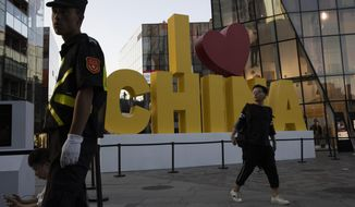 """In this Monday, Sept. 23, 2019, photo, a man walks past a """"I love China"""" decoration with a red heart shape at a trendy retail district in Beijing. Patriotic banners, elaborate flower displays and tightened security are all on tap as the Chinese capital prepares to mark the 70th anniversary of Communist Party rule on Tuesday, Oct. 1, 2019. (AP Photo/Ng Han Guan)"""