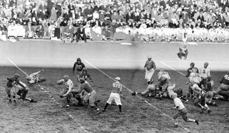 FILE - In this Nov. 20, 1938, file photo, Green Bay Packers halfback Cecil Isbell (17) gains 10-yards against the New York Giants during the first quarter of a professional football game at the Polo Grounds in New York. (AP Photo)