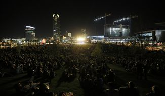 This Friday, Sept. 27, 2019, photo shows a view from the park's hill as Kings of Leon perform during the grand opening of Scissortail Park in downtown Oklahoma City. (Nate Billings/The Oklahoman via AP)