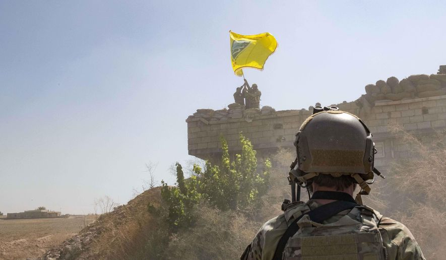 "In this Sept. 21, 2019, photo, released by the U.S. Army, a U.S. soldier oversees members of the Syrian Democratic Forces as they demolish a Kurdish fighters' fortification and raise a Tal Abyad Military Council flag over the outpost as part of the so-called ""safe zone"" near the Turkish border. (U.S. Army photo by Staff Sgt. Andrew Goedl via AP)"