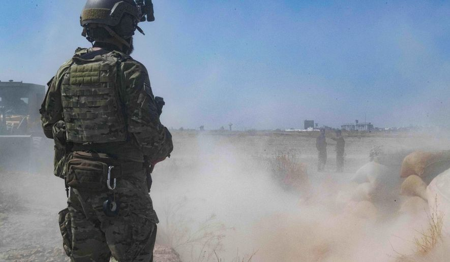 """In this Sept. 21, 2019, file photo, released by the U.S. Army, a U.S. soldier oversees members of the Syrian Democratic Forces as they demolish a Kurdish fighters' fortification as part of the so-called """"safe zone"""" near the Turkish border. (U.S. Army photo by Staff Sgt. Andrew Goedl via AP)"""