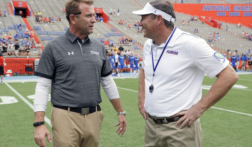 Towson head coach Rob Ambrose, left, and Florida head coach Dan Mullen greet each other at midfield before an NCAA college football game, Saturday, Sept. 28, 2019, in Gainesville, Fla. (AP Photo/John Raoux)