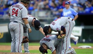 Minnesota Twins third baseman Luis Arraez (2) is checked on by teammates Willians Astudillo (64), Jorge Polanco (11) and Tyler Duffey, back, during the eighth inning of a baseball game against the Kansas City Royals at Kauffman Stadium in Kansas City, Mo., Saturday, Sept. 28, 2019. (AP Photo/Orlin Wagner)