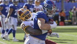 Washington Redskins' Landon Collins, left, tries to bring down New York Giants' Rhett Ellison during the second half of an NFL football game, Sunday, Sept. 29, 2019, in East Rutherford, N.J. (AP Photo/Bill Kostroun)