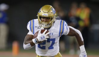In this file photo, UCLA running back Joshua Kelley (27) runs for a first down against Arizona in the second half during an NCAA college football game, Saturday, Sept. 28, 2019, in Tucson, Ariz. Arizona defeated UCLA 20-17. On Sept. 30, 2019, California Gov. Gavin Newsom said he had signed into law a bill that would let athletes at California universities make money from their images, names or likenesses, a move that defies NCAA officials who had called on the governor to veto the legislation. (AP Photo/Rick Scuteri)  ** FILE **