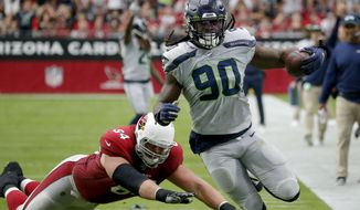 Seattle Seahawks outside linebacker Jadeveon Clowney (90) runs back an interception for a touchdown as Arizona Cardinals offensive guard J.R. Sweezy (64) defends during the first half of an NFL football game, Sunday, Sept. 29, 2019, in Glendale, Ariz. (AP Photo/Rick Scuteri)