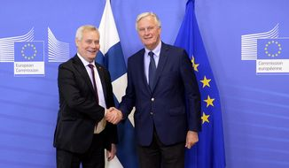 European Union chief Brexit negotiator Michel Barnier, right, shakes hands with Finnish Prime Minister Antti Rinne, left, at EU headquarters in Brussels, Friday, Sept. 27, 2019. (Johanna Geron, Pool Photo via AP)