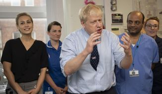 """Britain's Prime Minister Boris Johnson speaks during a visit to North Manchester General Hospital before the Conservative Conference, in Manchester, England, Sunday, Sept. 29, 2019. British Prime Minister Boris Johnson has urged calm as tempers flare in the debate over Britain's departure from the European Union, even though tempers are flaring over what he said. A defiant Johnson told the BBC on Sunday that the """"best thing for the country and for people's overall psychological health would be to get Brexit done."""" (Andy Stenning/Pool Photo via AP)"""