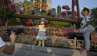 "In this Saturday, Sept. 28, 2019, photo, Chinese children pose with Chinese national flags near a floral display for the upcoming 70th anniversary of the Founding of the People's Republic of China in Beijing. Chinese President Xi Jinping has an ambitious goal for China: to achieve ""national rejuvenation"" as a strong and prosperous nation by 2049, which would be the 100th anniversary of Communist Party rule. One problem: U.S. Donald Trump wants to make the United States great again too. (AP Photo/Ng Han Guan)"