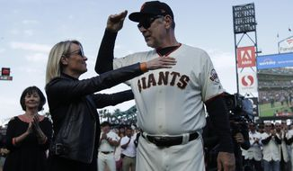 San Francisco Giants manager Bruce Bochy, right, hugs his wife Kim during a ceremony honoring Bochy after a baseball game between the Giants and the Los Angeles Dodgers in San Francisco, Sunday, Sept. 29, 2019. (AP Photo/Jeff Chiu, Pool)