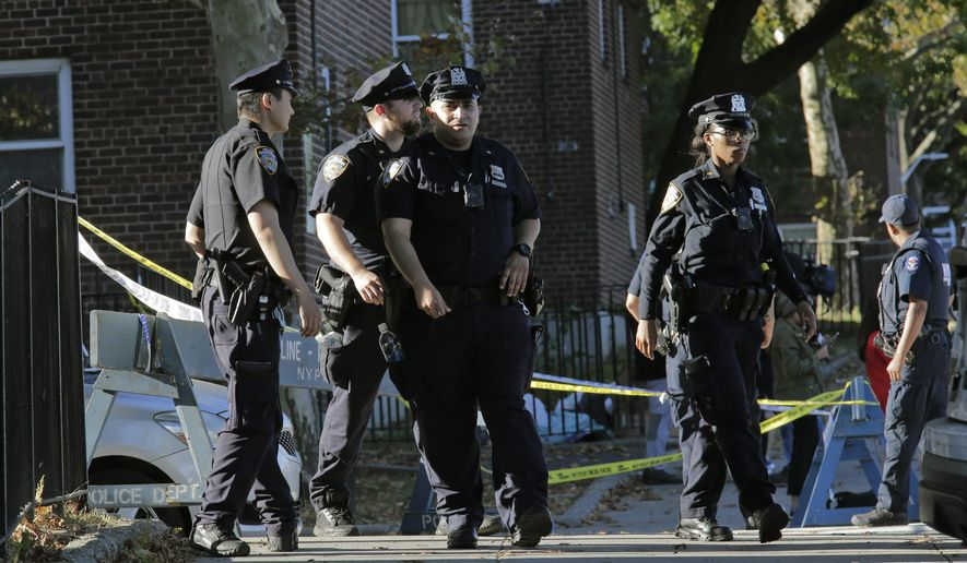 Emergency personnel walk near the scene of a fatal shooting of a New York City police officer in the Bronx borough of New York, Sunday, Sept. 29, 2019.  (AP Photo/Seth Wenig)