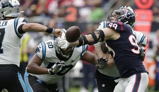 Houston Texans defensive end J.J. Watt (99) knocks the ball away from Carolina Panthers quarterback Kyle Allen (7) during the second half of an NFL football game Sunday, Sept. 29, 2019, in Houston. Watt recovered the fumble. (AP Photo/Michael Wyke)