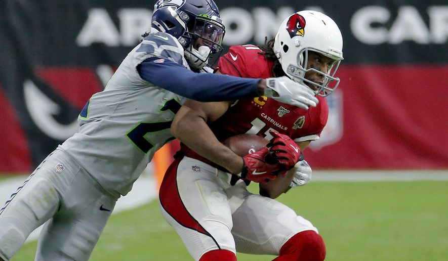 Arizona Cardinals wide receiver Larry Fitzgerald (11) pulls in a catch as Seattle Seahawks cornerback Tre Flowers (21) defends during the second half of an NFL football game, Sunday, Sept. 29, 2019, in Glendale, Ariz. (AP Photo/Rick Scuteri)