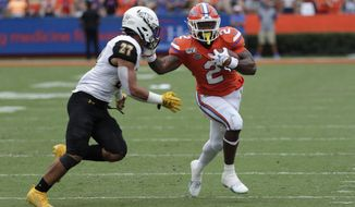 Florida running back Lamical Perine, right, tries to avoid Towson safety S.J. Brown II (27) during the first half of an NCAA college football game, Saturday, Sept. 28, 2019, in Gainesville, Fla. (AP Photo/John Raoux)