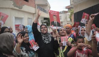 In this Saturday, Sept. 21, 2019 photo, supporters of jailed media magnate Nabil Karoui chant for his freedom and carry posters which were provided to them by his campaign officials, in Nabeul, west of Tunis, Tunisia.  The two final contenders for Tunisia's upcoming presidential runoff vote, pitches a professor who refuses to campaign, against a media mogul who can only campaign from his jail cell. (AP Photo/Mosa'ab Elshamy)