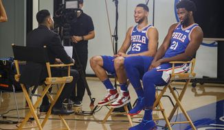 Philadelphia 76ers' Ben Simmons, left, and Joel Embiid, right, conduct interviews during media day at the NBA basketball team's practice facility, Monday, Sept. 30, 2019, in Camden. (AP Photo/Chris Szagola)