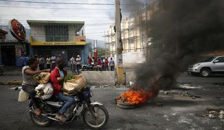 A motorcyclist drives past a burning barricade during a nationwide push to block streets and paralyze the country's economy as protesters press for President Jovenel Moise to give up power, in Port-au-Prince, Haiti, Monday, Sept. 30, 2019. Opposition leaders and supporters say they are angry about public corruption, spiraling inflation and a dwindling supply of gasoline that has forced many gas stations in the capital to close as suppliers demand the cash-strapped government pay them more than $100 million owed. (AP Photo/Rebecca Blackwell)