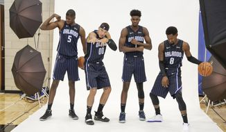 Orlando Magic players, from left, Mo Bamba (5), Aaron Gordon (00), Jonathan Isaac and Terrence Ross (31) have some fun posing for photos during the NBA basketball team's media day, Monday, Sept. 30, 2019, in Orlando, Fla. (AP Photo/John Raoux)