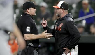 Baltimore Orioles manager Brandon Hyde, right, talks to home plate umpire Dan Bellino after Orioles' Renato Nunez was thrown out by Toronto Blue Jays' Bo Bichette at first base to end the third inning of a baseball game, Thursday, Sept. 19, 2019, in Baltimore. (AP Photo/Julio Cortez)