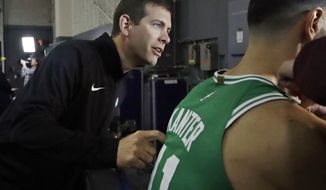 Boston Celtics head coach Brad Stevens leans in as Enes Kanter prepares to be filmed during the NBA basketball team's media day, Monday, Sept. 30, 2019 in Canton, Mass. (AP Photo/Elise Amendola)