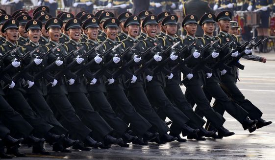 Chinese soldiers rehearse before the start of a parade to mark the 70th anniversary of the founding of the People's Republic of China in Beijing on Tuesday, Oct. 1, 2019. (AP Photo/Ng Han Guan)