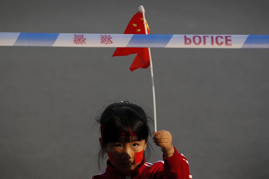 A child waves a national flag behind a police barricade line as Chinese military vehicles and floats in preparation for the parade for the 70th anniversary of the founding of the People's Republic of China, in Beijing, Tuesday, Oct. 1, 2019. China's ruling Communist Party is preparing to celebrate its 70th anniversary in power with a parade showcasing the country's economic growth and newest weapons.(AP Photo/Andy Wong)