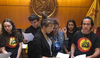 High school student Artemisio Romero y Carver, right, of Santa Fe, leads environmental activists in a climate change protest song as they deliver a letter of demands to the office of New Mexico Gov. Michelle Lujan Grisham in Santa Fe, N.M., Monday, Sept. 30, 2019. Student activists including several Native American high school students urged New Mexico's Democratic governor to take more aggressive action to address climate change, insisting that her targets for reducing pollution from vehicles, power plants and oil rigs are not ambitious enough. State government and school districts in New Mexico rely heavily on income from oil and natural gas production. (AP Photo/Morgan Lee)