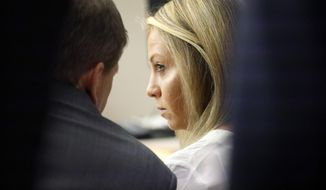Former Dallas police officer Amber Guyger listens to her attorney Toby Shook during her trial at the Frank Crowley Courts Building in Dallas, Saturday, Sept. 28, 2019.  Guyger shot and killed Botham Jean, an unarmed 26-year-old neighbor in his own apartment last year. She said she mistook his fourth-floor apartment for her own. (Tom Fox/The Dallas Morning News via AP, Pool)