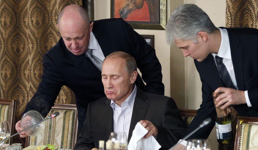 In this Friday, Nov. 11, 2011, file photo, businessman Yevgeny Prigozhin, left, serves food to then-Russian Prime Minister Vladimir Putin, center, during dinner at Prigozhin's restaurant outside Moscow, Russia. (AP Photo/Misha Japaridze, Pool, File)