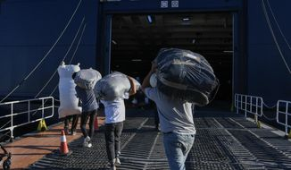 Refugees and Migrants carry their belongings as they disembark on a ferry with destination the port of Piraeus, on the northeastern Aegean island of Lesbos, Greece, Monday, Sept. 30, 2019. Authorities have been moving hundreds of migrants and refugees deemed to be vulnerable from the overcrowded Moria camp in Lesbos island to camps on the mainland. (AP Photo/Michael Varaklas)