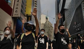 Protesters display opened palm with five fingers, signifying the five demands of protesters at a main street in Hong Kong, Sunday, Sept. 29, 2019. Riot police fired tear gas Sunday after a large crowd of protesters at a Hong Kong shopping district ignored warnings to disperse in a second straight day of clashes, sparking fears of more violence ahead of China's National Day. (AP Photo/Vincent Yu)