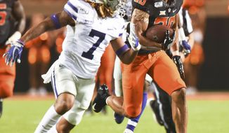 Oklahoma State running back Chuba Hubbard (30) looks to Kansas State defensive back Kevion McGee (7), while breaking free for a 84 yard run during the third quarter of an NCAA college football game in Stillwater, Okla., Saturday, Sept. 28, 2019. Hubbard led Oklahoma State rushing with 296 yards in the 26-13 win over Kansas State. (AP Photo/Brody Schmidt)