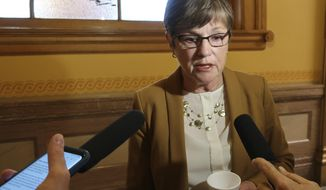 Kansas Gov. Laura Kelly talks to reporters, Monday, Sept. 30, 2019, at the Statehouse in Topeka, Kansas. Attorney General Derek Schmidt has issued a legal opinion saying that a new and aggressive policy imposed by Kelly's administration for taxing online sales is invalid. (AP Photo/John Hanna)