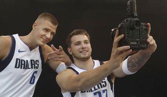 Dallas Mavericks Luka Doncic (77) of Slovenia and teammate Kristaps Porzingis of Latvia make a photo of themselves during an NBA basketball media day in Dallas, Monday, Sept. 30, 2019. (AP Photo/LM Otero)