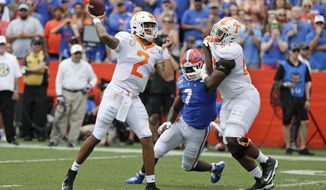 Tennessee quarterback Jarrett Guarantano (2) throws a pass as offensive lineman Wanya Morris, right, tries to block Florida linebacker Jeremiah Moon (7) during the first half of an NCAA college football game, Saturday, Sept. 21, 2019, in Gainesville, Fla. (AP Photo/John Raoux)