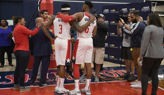 Washington Wizards' Bradley Beal (3) and Troy Brown Jr. (6) talks to members of the media during an NBA basketball media day, Monday, Sept. 30, 2019, in Washington. (AP Photo/Nick Wass)