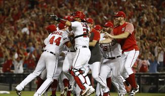 Members of the Washington Nationals celebrate after winning a National League wild-card baseball game against the Milwaukee Brewers, Tuesday, Oct. 1, 2019, in Washington. Washington won 4-3. (AP Photo/Patrick Semansky)