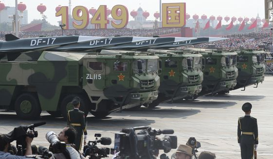 Military vehicles, carrying DF-17, roll down as members of a Chinese military honor guard march during the parade to commemorate the 70th anniversary of the founding of Communist China in Beijing, Tuesday, Oct. 1, 2019.  China's military has shown off a new hypersonic ballistic nuclear missile believed capable of breaching all existing anti-missile shields deployed by the U.S. and its allies. The vehicle-mounted DF-17 was among weapons displayed Tuesday in a massive military parade marking the 70th anniversary of the founding of the Chinese state.(AP Photo/Ng Han Guan)
