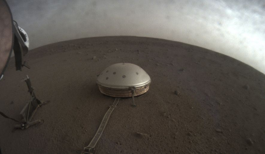 This April 25, 2019, file photo made available by NASA shows the InSight lander's dome-covered seismometer, known as SEIS, on Mars. On Tuesday, Oct. 1, 2019, scientists released an audio sampling of marsquakes and other sounds recorded by the probe. (NASA/JPL-Caltech via AP)