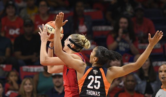 Washington Mystics forward Elena Delle Donne, back, goes to the basket past Connecticut Sun forward Alyssa Thomas (25) in the first half of Game 2 of basketball's WNBA Finals, Tuesday, Oct. 1, 2019, in Washington. (AP Photo/Nick Wass)