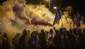 Pro-independence demonstrators, some of them holding flares, march as they take part in a demonstration in Girona, Spain, Tuesday Oct. 1, 2019. A few hundred Catalan secession supporters are marching in the northeastern city of Girona to mark two years since a banned independence referendum that shook Spanish politics. (AP Photo/Emilio Morenatti)