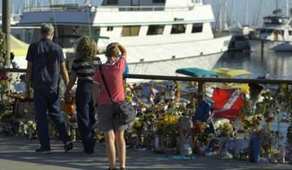 """FILE - In this Sept. 6, 2019 file photo people visit a growing memorial to the victims who died aboard the dive boat Conception as its sister boat Vision sits in the background, in Santa Barbara, Calif. The owner of the scuba diving boat company has announced an indefinite suspension of its fleet in the wake of the fatal boat fire off the Southern California coast that killed 34 people. Truth Aquatics Inc. says Tuesday, Oct. 1, 2019 on its Facebook page that the company will """"dedicate our entire efforts to make our boats models of new regulations"""" in collaboration with the Coast Guard and the National Transportation Safety Board. (AP Photo/Mark J. Terrill,File)"""
