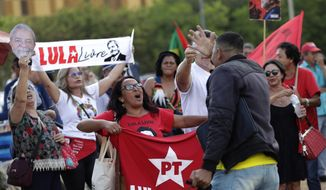 A supporter of Operation Car Wash, rights, argues with supporters of former President Luiz Inacio Lula da Silva, during act in support of operation Car Wash and former judge Sergio Moro, in front of Supreme Court headquarters, in Brasilia, Brazil, Wednesday, Sept. 25, 2019. Brazil's Supreme Court will decide about a prisoner involved in the Car Wash operation, an anti-corruption investigation that managed to jail politicians and businessmen all over Latin America, that could open a door for others arrested during the operation, to appeal their sentences. The former president was jailed as a result of the Car Wash investigations. (AP Photo/Eraldo Peres)
