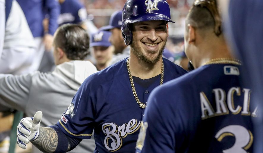 Milwaukee Brewers' Yasmani Grandal, center, celebrates with teammate Orlando Arcia (3) after hitting a two-run home run during the first inning of a National League wild card baseball game against the Washington Nationals at Nationals Park, Tuesday, Oct. 1, 2019, in Washington. (AP Photo/Andrew Harnik)