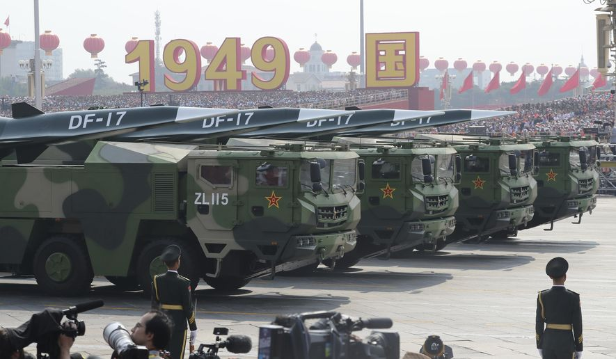 Military vehicles, carrying DF-17, roll down as members of a Chinese military honor guard march during the parade to commemorate the 70th anniversary of the founding of Communist China in Beijing, Tuesday, Oct. 1, 2019. (AP Photo/Ng Han Guan)