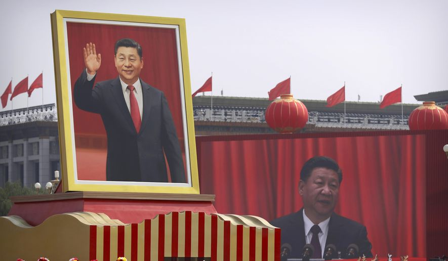 Participants cheer beneath a large portrait of Chinese President Xi Jinping during a parade to commemorate the 70th anniversary of the founding of Communist China in Beijing, Tuesday, Oct. 1, 2019. Trucks carrying weapons including a nuclear-armed missile designed to evade U.S. defenses rumbled through Beijing as the Communist Party celebrated its 70th anniversary in power with a parade Tuesday that showcased China's ambition as a rising global force. (AP Photo/Mark Schiefelbein)