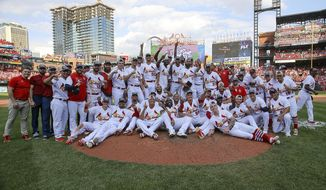 Members of the St. Louis Cardinals pose for a group picture as they celebrate their victory after a baseball game Sunday, Sept. 29, 2019, in St. Louis. The Cardinals clinched the NL Central on the final day of the regular season, to win their first division title since 2015 with a 9-0 victory over the Chicago Cubs. (AP Photo/Scott Kane)