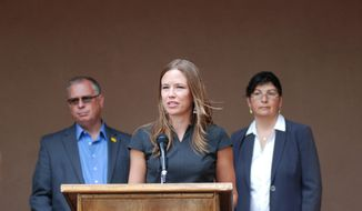 New Mexico Taxation and Revenue Secretary Stephanie Schardin Clarke, center, foreground, Motor Vehicle Division Director Alicia Ortiz, right, and state Sen. Daniel Ivey-Soto, left, announce changes to state driver's license application requirements at a news conference on Tuesday, Oct. 1, 2019, in Santa Fe, N.M. New Mexico is making it easier for residents to obtain a basic driver's license that is recognized by state agencies and private businesses but will not be valid for commercial airline travel starting in October 2020. Requirements won't change for licenses that are compliant with federal Real ID standards that ensure continued access next year to commercial airliners and some federal facilities. (AP Photo/Morgan Lee)