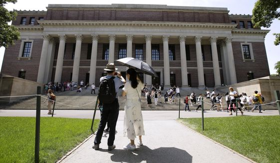 In this July 16, 2019, photo, people stop to record images of Widener Library on the campus of Harvard University in Cambridge, Mass. U.S. District Judge Allison D. Burroughs ruled, Tuesday, Oct. 1, 2019, that Harvard does not discriminate against Asian Americans in its admissions process. The judge issued the ruling in a 2014 lawsuit that alleged Harvard holds Asian American applicants to a higher standard than students of other races. Burroughs said Harvard's admissions process is not perfect but passes constitutional muster. (AP Photo/Steven Senne) **FILE**