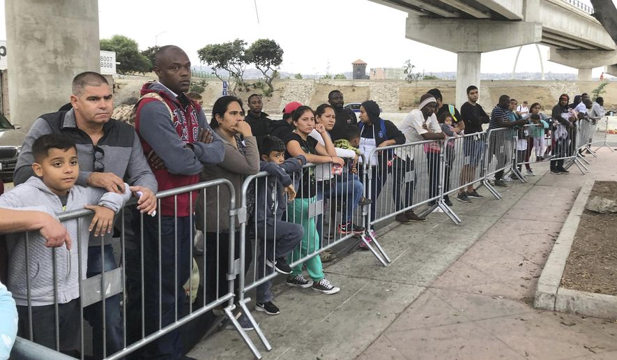In this Sept. 26, 2019, file photo asylum seekers in Tijuana, Mexico, listen to names being called from a waiting list to claim asylum at a border crossing in San Diego. (AP Photo/Elliot Spagat, File)